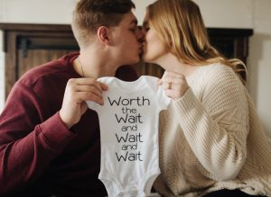 Husband and wife kissing while holding a baby onsie
